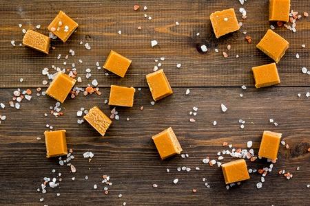 Trendy dessert. Salted caramel. Caramel cubes sprinkled by salt crystals on dark wooden background top view Stock Photo