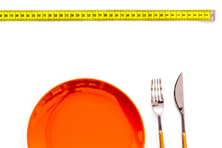 Diet for weight loss concept. Proper nutrition. Medical starvation. Empty plate with fork and knife near measuring tape on white background top view. Фото со стока