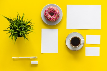 Come up with brand identity. Blank stationery for branding near coffee and donut on yellow background top view mockup pattern.