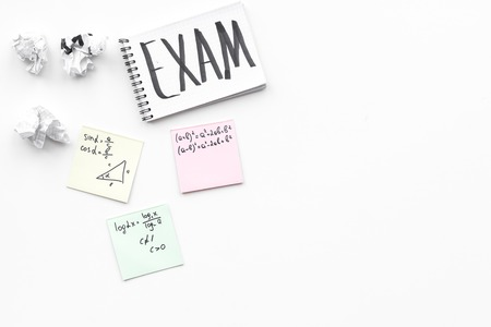 Exam concept. Lettering Exam in notebook on students work desk on white background top view. Stockfoto