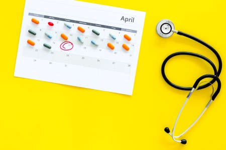 Planning medical examination concept. Regular medical examinations. Calendar with date circled, pills and stethoscope on yellow background top view copy space Stock Photo