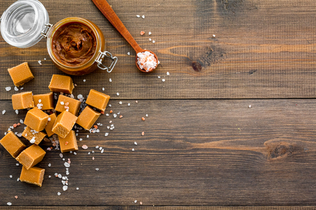 Contrast of flavors. The combination of salty and sweet. Caramel sauce in glass jar near caramel cubes on dark wooden background top view copy space