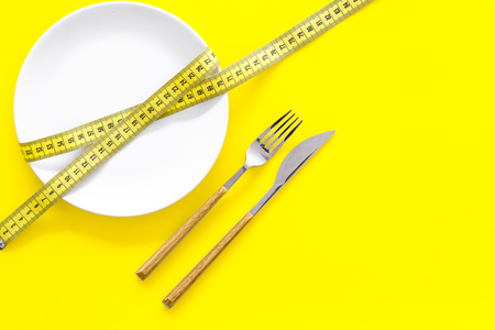 Diet for weight loss concept. Proper nutrition. Medical starvation. Empty plate with fork and knife near measuring tape on yellow background top view.