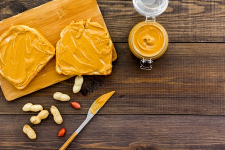 Spread nut butter on sandwich. Toast, knife and glass jar with nut paste, nuts on dark wooden background copy space
