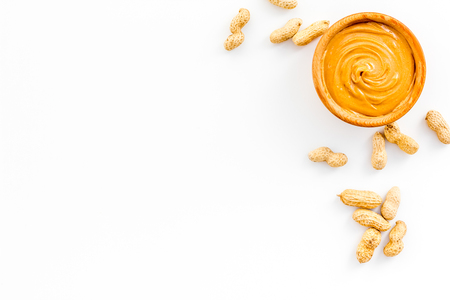 Product for hearty breakfast. High-calorie product. Peanut butter in bowl near nuts in shell on white background top view space for text