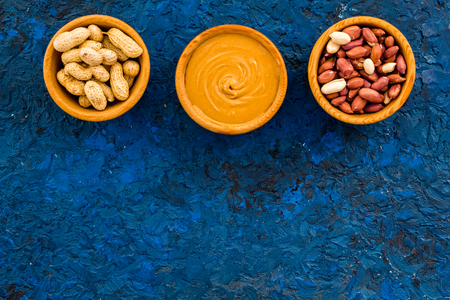 Peanut paste concept. Bowls with butter, nuts in shell, peeled nuts on blue background top view copy space