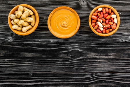 Peanut paste concept. Bowls with butter, nuts in shell, peeled nuts on black wooden background top view copy space