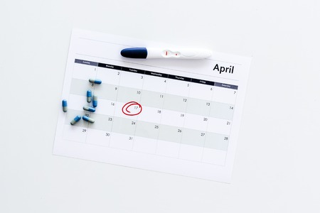 Planning pregnancy. Positive pregnancy test near calendar page and pills on white background top view space for text