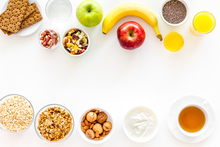 Ingredients for healthy breakfast. Fruits, oatmeal, yogurt, nuts, crispbreads, chia on white background top view copy space