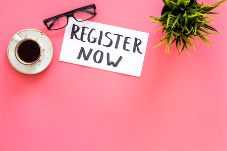 Membership concept. Template for registration. Register now hand lettering icon on word desk with glasses, coffee, plant on pink background top view space for text Stockfoto