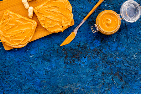 Make toast with nut paste. Two toasted, knife and glass jar with nut paste, nuts on blue background copy space Stock Photo