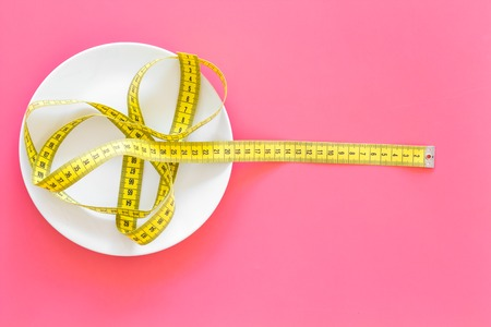 Proper nutrition for slimming. Empty plate and measuring tape on pink background top view copy space