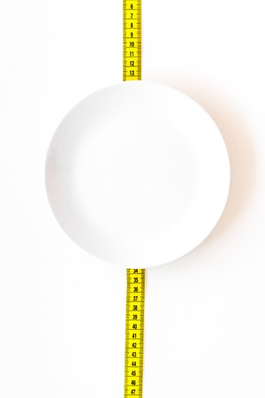 Proper nutrition for slimming. Empty plate and measuring tape on white background top view mockup Stock Photo