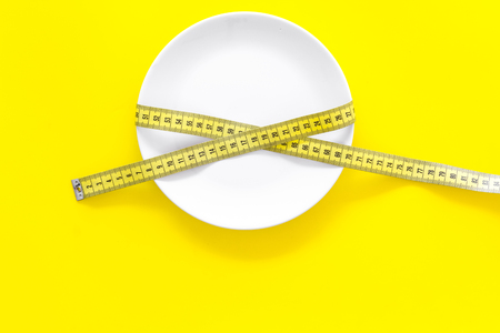 Proper nutrition for slimming. Empty plate and measuring tape on yellow background top view copy space