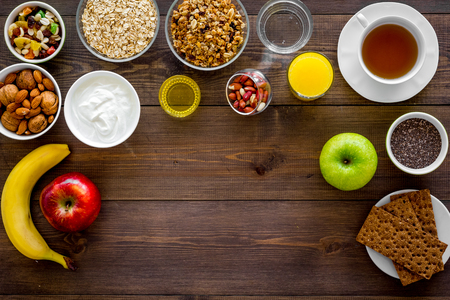 Set of products for healthy vegetarian breakfast. Fruits, oatmeal, yogurt, nuts, crispbreads, chia on dark wooden background top view space for text