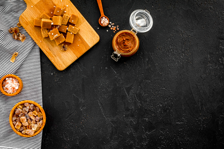 Salted caramel background. Melted caramel in glass jar, caramel cubes on cutting board, sugar and salt on black desk top view copy space Banco de Imagens