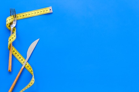 Proper nutrition for slimming. Fork and knife with wound measuring tape on blue background top view copy space 스톡 콘텐츠