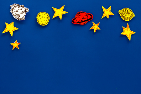 Space concept. Drawn stars, planets, asteroids on blue outer space background top view copy space