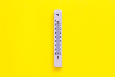 Thermometer for measuring temperature outdoor on yellow background top view copy space