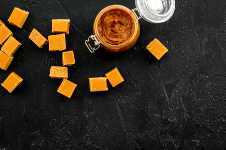 Caramel sauce in glass jar near caramel cubes on black background top view.