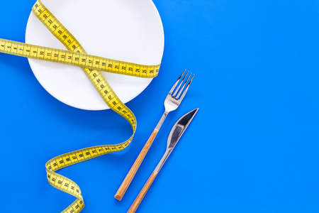 Diet for weight loss concept. Proper nutrition. Medical starvation. Empty plate with fork and knife near measuring tape on blue background top view copy space Фото со стока