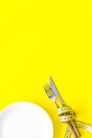 Diet for weight loss concept. Proper nutrition. Medical starvation. Empty plate with fork and knife near measuring tape on yellow background top view mockup