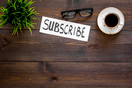Email subscribe concept. Hand lettering subscribe on work desk with plant, glasses, cup of coffee on dark wooden background top view copy space