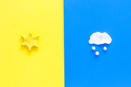 Good and bad weather concept. Template for forecast. Sun vs snow cloud on yellow and blue background top view copy space