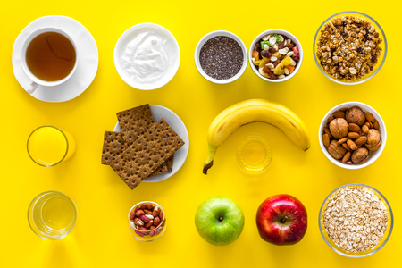 Layout of products for healthy and hearty breakfast. Fruits, oatmeal, yogurt, nuts, crispbreads, chia on yellow background top view copy space Stock Photo - 102014572