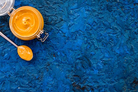 Nut butter in glass jar and spoon with butter on blue background top view copy space