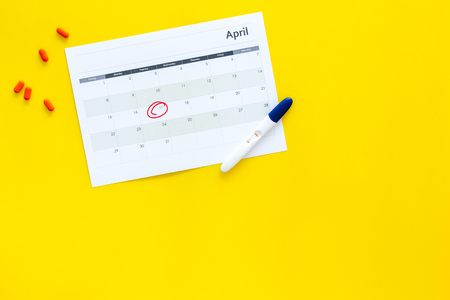 Planning pregnancy. Positive pregnancy test near calendar page and pills on yellow background top view copy space Stock Photo