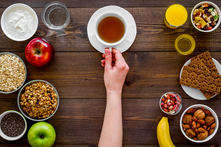 Set of products for healthy vegetarian breakfast. Fruits, oatmeal, yogurt, nuts, crispbreads, chia on dark wooden background top view. Hand takes tea