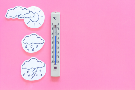 Weather forecast concept. Air temperature. Thermometer among cloud and lightening, sun, rainy clouds on pink background top view copy space