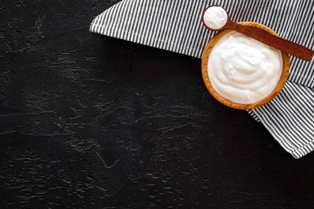 Food helps digestion. Greek yogurt in brown bowl near spoon on blue tablecloth, black background top view.