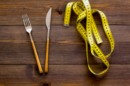 Proper nutrition for slimming. Fork, knife and measuring tape on dark wooden background top view.