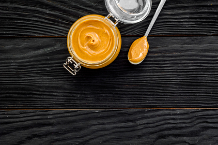 Nut butter in glass jar and spoon with butter on black wooden background top view. Stock Photo