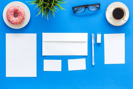 Come up with brand identity. Blank stationery for branding near coffee and donut on blue background top view. Stockfoto