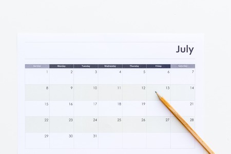 Planning. Point the date in calendar by pencil. Set the goal. Choose date. Calendar on white background top view.