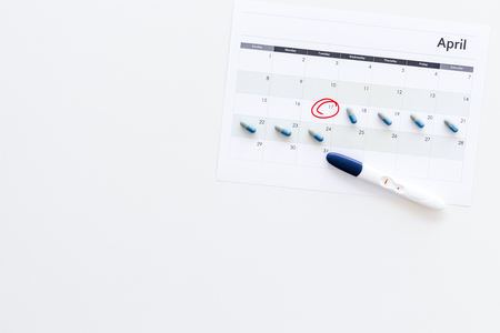 Planning pregnancy. Positive pregnancy test near calendar page and pills on white background top view.