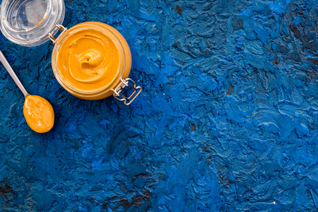 Nut butter in glass jar and spoon with butter on blue background top view.