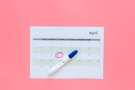 Planning pregnancy. Positive pregnancy test near calendar page on pink background top view.