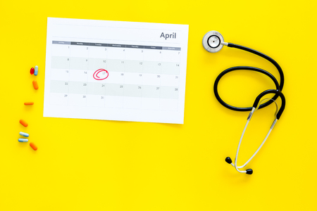 Planning medical examination concept. Regular medical examinations. Calendar with date circled and stethoscope on yellow background top view. Stock Photo