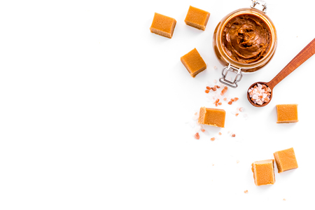 Contrast of flavors. The combination of salty and sweet. Caramel sauce in glass jar near caramel cubes on white background top view.