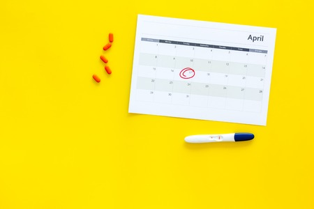 Planning pregnancy. Positive pregnancy test near calendar page and pills on yellow background top view. Stock Photo - 102045611