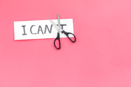 I can concept. Motivate yourself, believe in yourself. Scissors cut the letter t of written word I cant. Pink background top view.