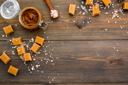 Contrast of flavors. The combination of salty and sweet. Caramel sauce in glass jar near caramel cubes on dark wooden background top view.
