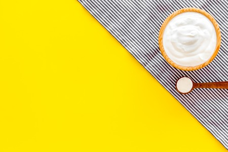 Food helps digestion. Greek yogurt in brown bowl near spoon on blue tablecloth, yellow background top view. Reklamní fotografie