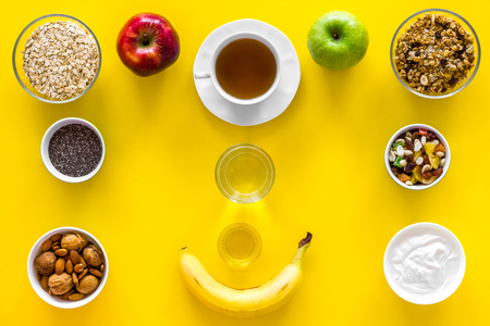 Layout of products for healthy and hearty breakfast. Fruits, oatmeal, yogurt, nuts, crispbreads, chia on yellow background top view. 写真素材