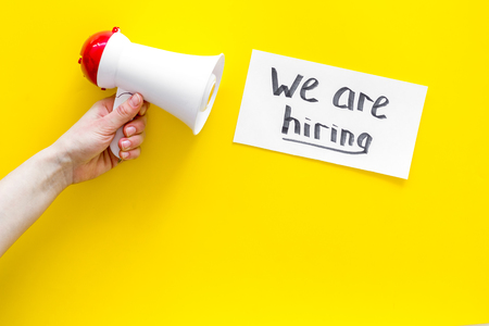 Job recruiting advertisement. We are hiring lettering near megaphone on yellow background top view. Stock Photo