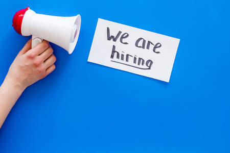 Job recruiting advertisement. We are hiring lettering near megaphone on blue background top view.